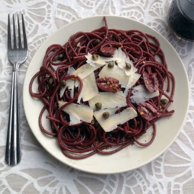 Drunken spaghetti (red wine spaghetti) with olives, capers, and shaved parmesan